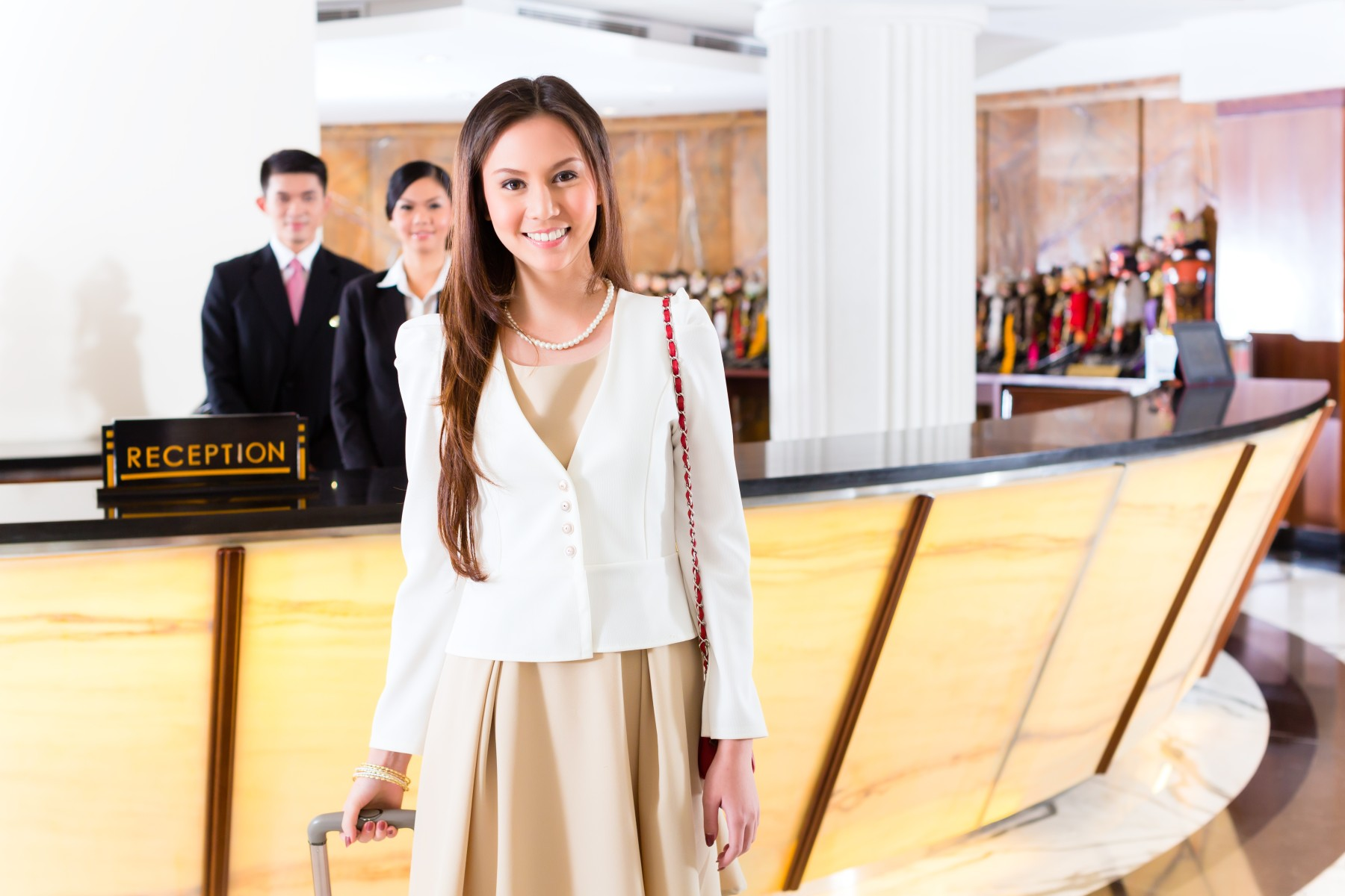 Asian Chinese woman arriving at front desk of luxury hotel in bu