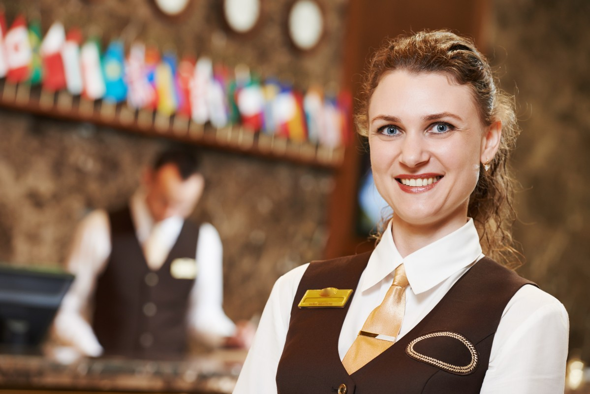 Happy receptionist female worker portrait standing at hotel coun