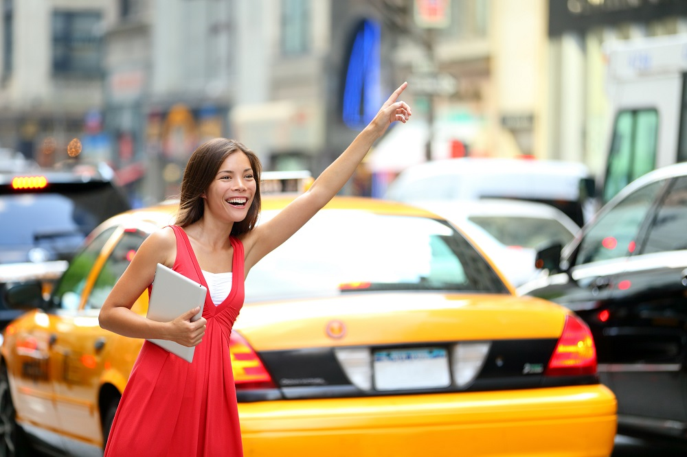 Girl calling taxi cab in New York City, holding tablet pc comput