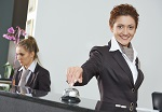 Happy female receptionist worker standing at hotel counter with
