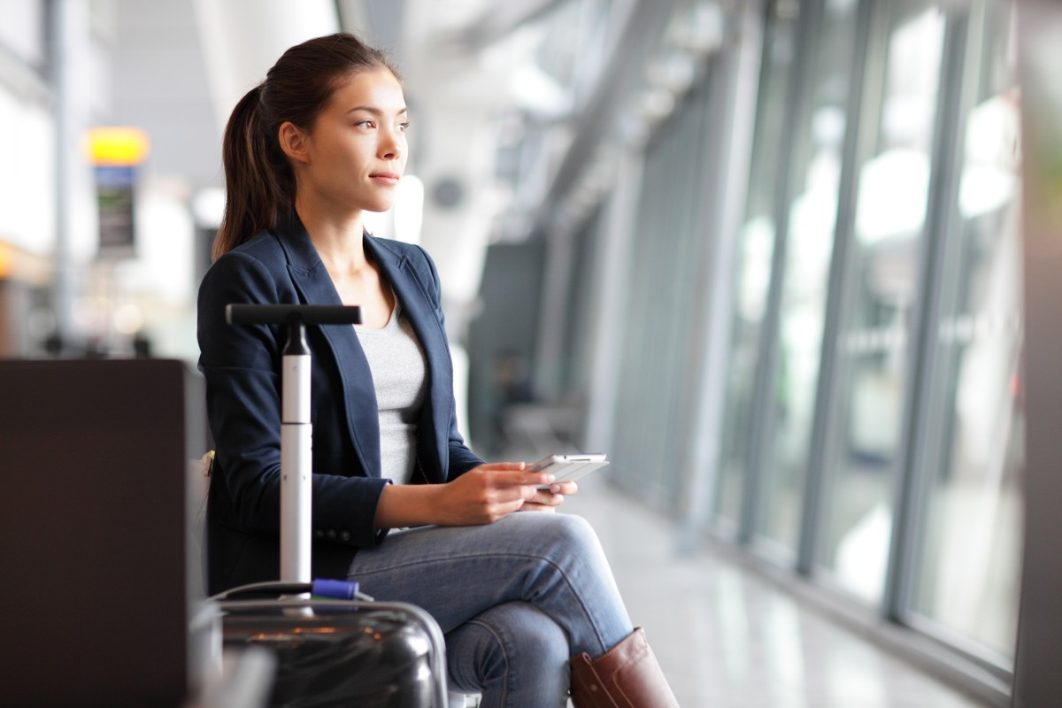 Passenger traveler woman in airport waiting for air travel using
