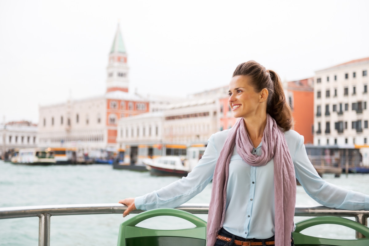 Smiling young woman travel by vaporetto in venice italy